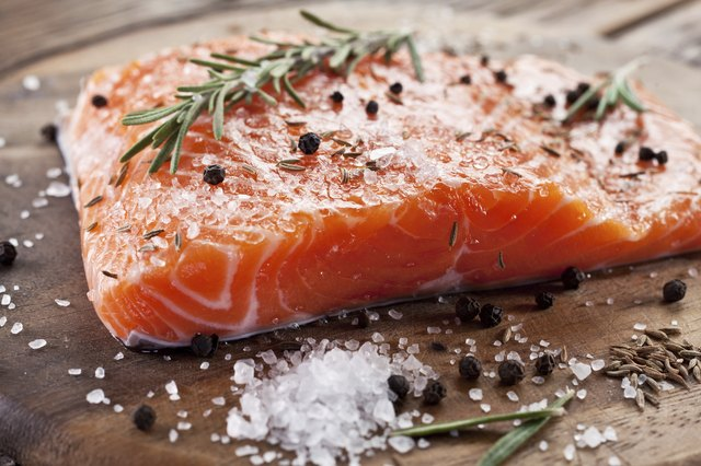 A raw filet of salmon covered in rosemary, peppercorns and salt