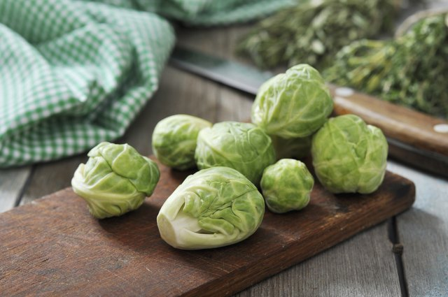 A bunch of Brussels sprouts on a wooden cutting board