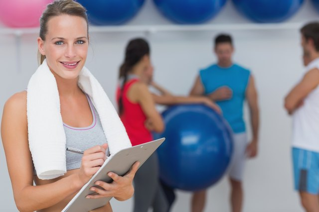 Female trainer holding clipboard with fitness class in background