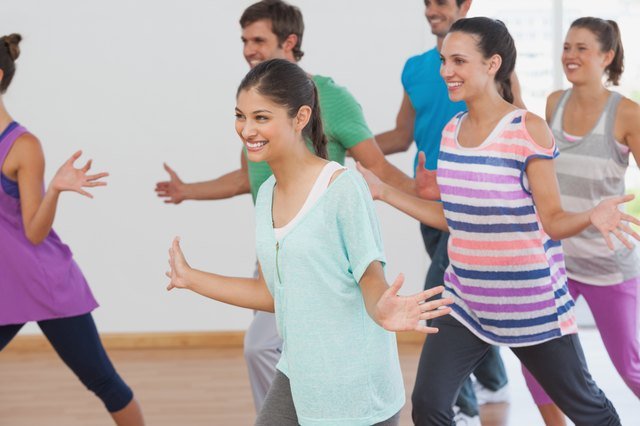 Cheerful fitness class and instructor doing pilates