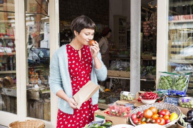 Woman smelling fresh tomato at organic farm shop.