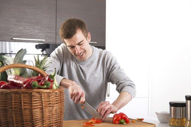 Junger Mann beim Paprika schneiden in Küche