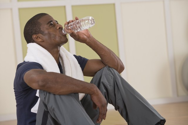 Man drinking bottled water and towel