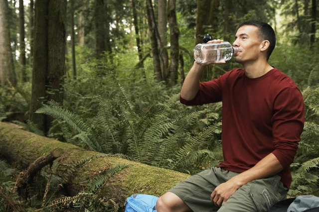 Young man sitting on log in forest, drinking water