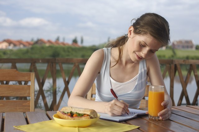 Woman eating and sitting on terrace writing