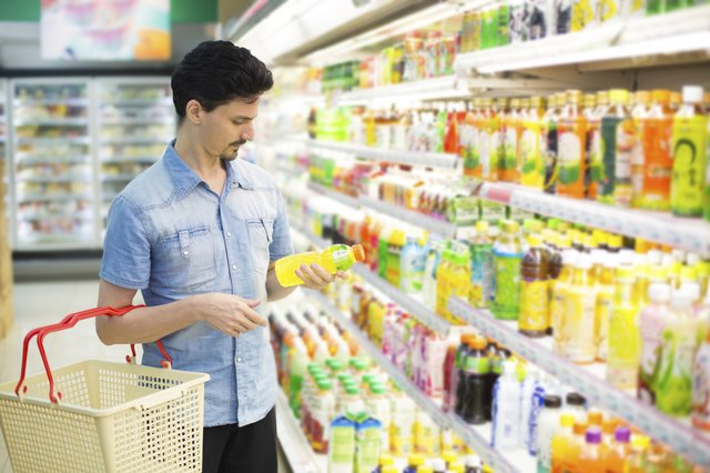 man in  supermarket buying a bottle of juice