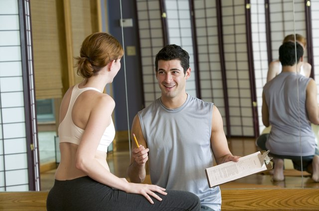Woman at gym conversing with personal trainer