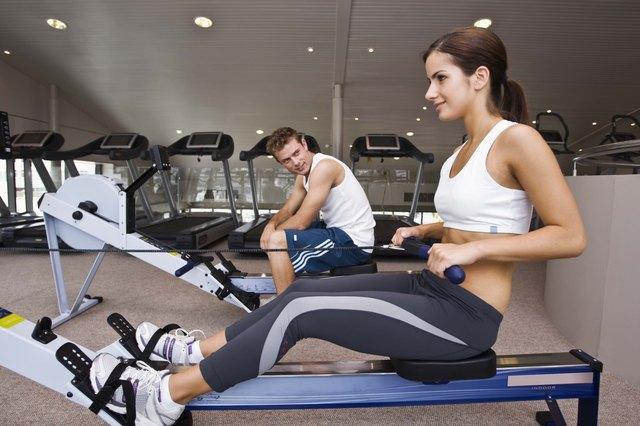 Man watching woman on rowing machine at gym