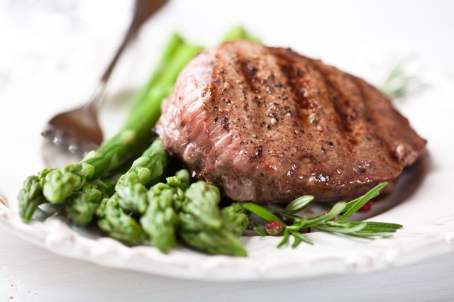 Juicy grilled steak on green asparagus