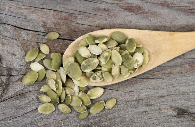 Pumpkin seeds in a wooden spoon.