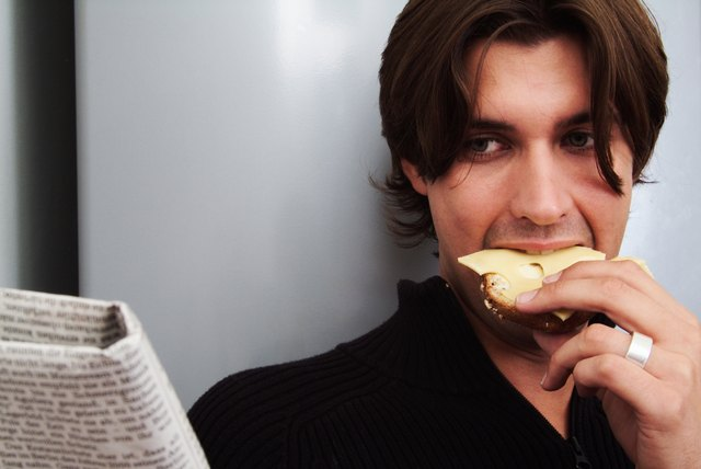 Young man reading newspaper eating bread and cheese