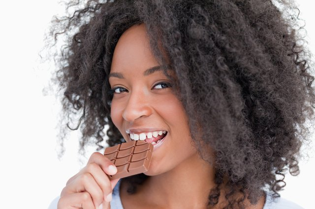 Young woman looking at the camera while eating chocolate