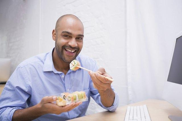 Businessman eating sushi at office desk