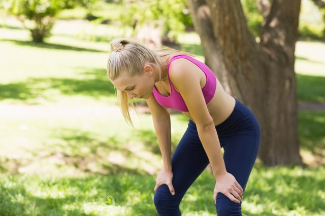 Tired woman in sports bra standing at park