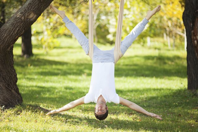 Anti-gravity Yoga, man doing exercises in the park
