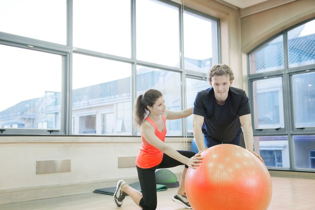 Fitness trainer helping young man with exercises on a fitness ball