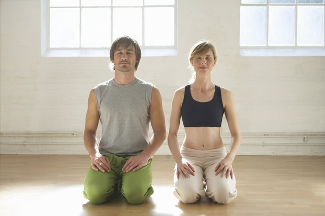 Man and woman kneeling indoors, eyes closed