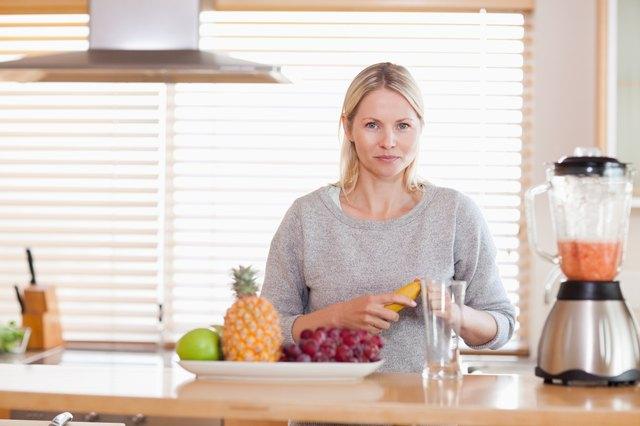 Woman preparing fruits for the blender