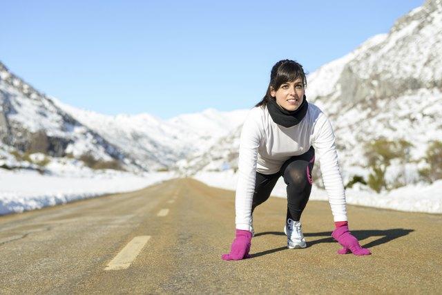 Woman run in winter landscape road