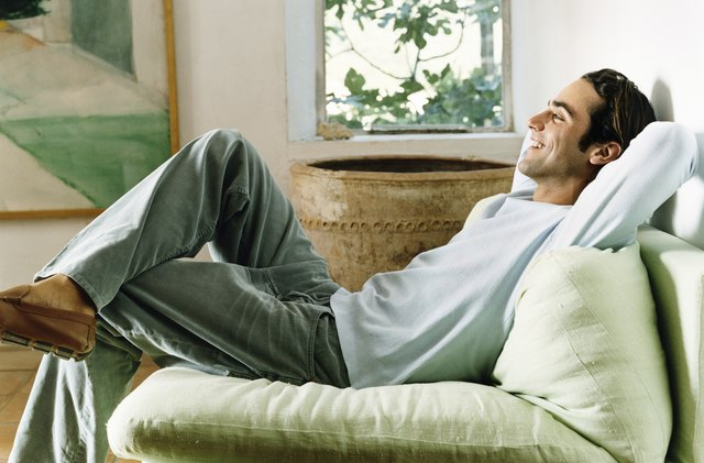 Man Relaxing in an Armchair in a Living Room with His Hands Behind His Head