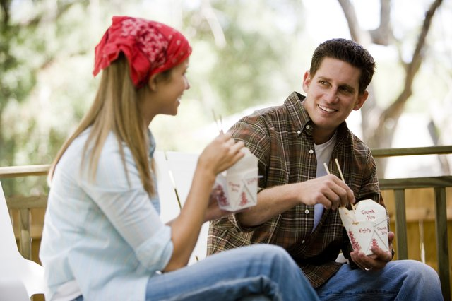 Cheerful young couple eating noodles on armchairs