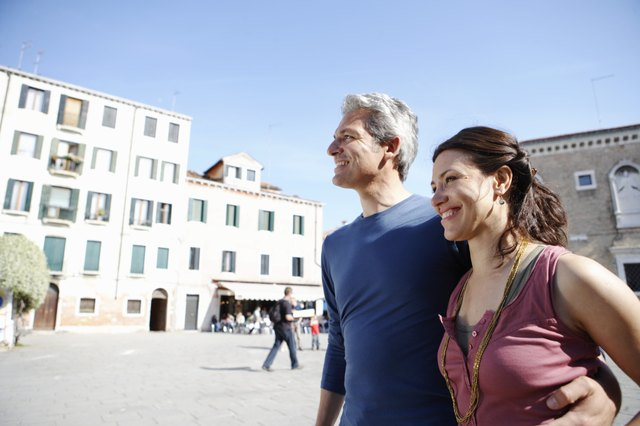 Italy, Venice, couple walking with arms around each other's waist