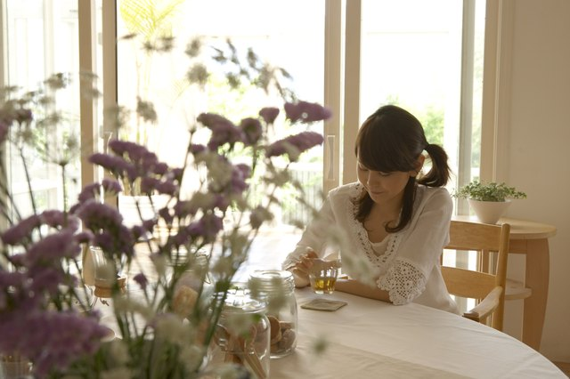 Woman with cup of tea, sitting at table in home, flowers in foreground