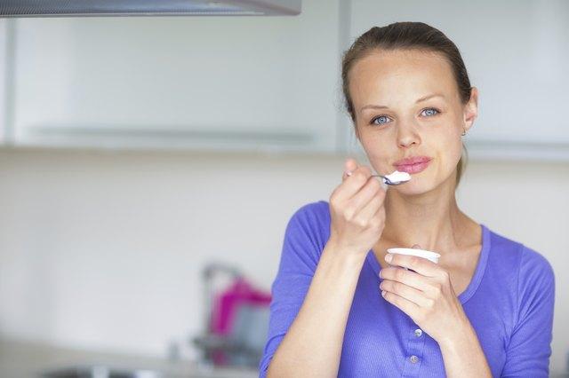 Happy young woman eating yogurt