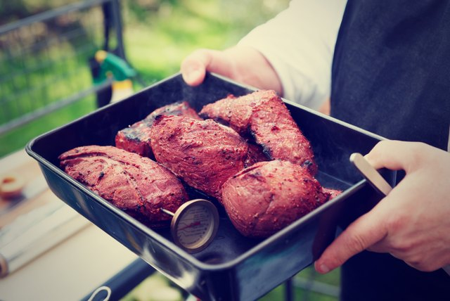 Chef holding a tray with cooked meat, toned