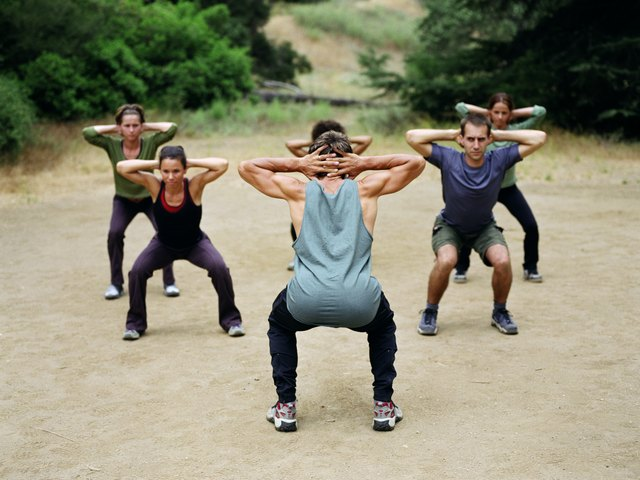 Man leading group of people in boot camp exercises, rear view