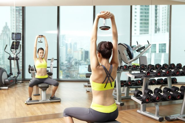 Young woman lifting weights upwards