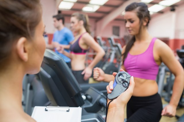Instructor using stopwatch in gym