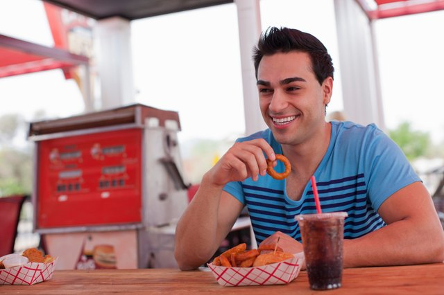Young man eating onion rings in diner, smiling