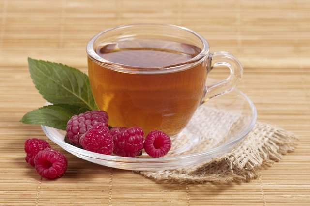Fruit tea in cup with raspberry