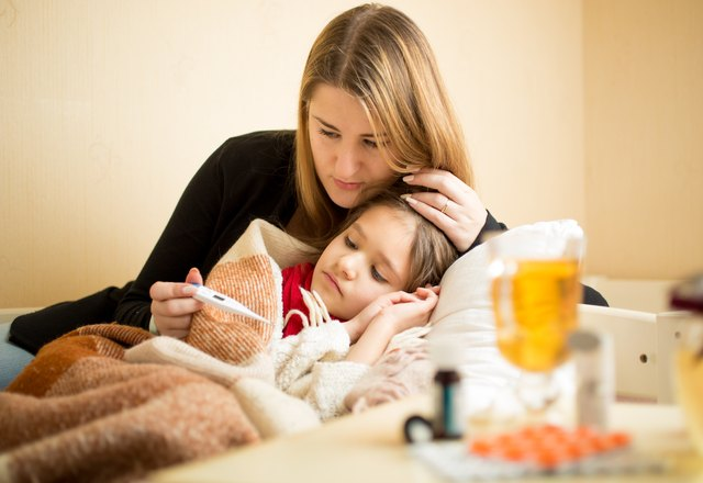 mother checking temperature of sick daughter lying in bed
