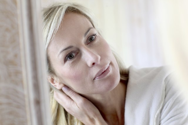 Mature blonde woman preserving its skin in bathroom