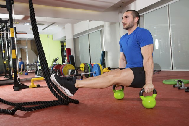 Crossfit fitness man L-sits Kettlebells L sits exercise