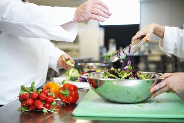 Chefs preparing salad in kitchen, mid section