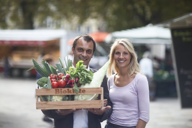 Couple walking with box of vegetables from market