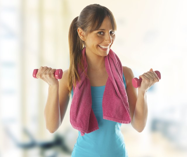 Smiling fitness woman lifting weights at gym