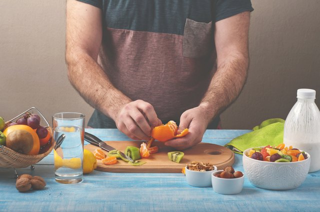 Man preparing a fruit salad in the kitchen at home