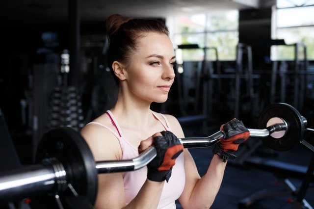 Young beautiful woman doing biceps curl with EZ curl bar in a gym. Athletic girl doing workout in a fitness center