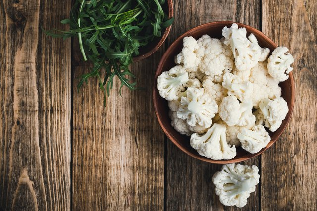 Fresh organic cauliflower cut into small pieces in a bowl. Vegetarian recipe or menu background with copy space
