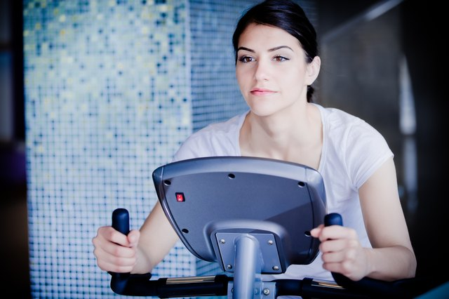 Woman riding an exercise bike in gym.Cardio and fat loss
