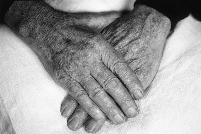 Hands of an elderly person one on top of the other (black and white)