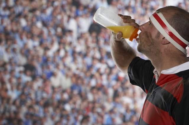 Rugby player drinking from water bottle, side view