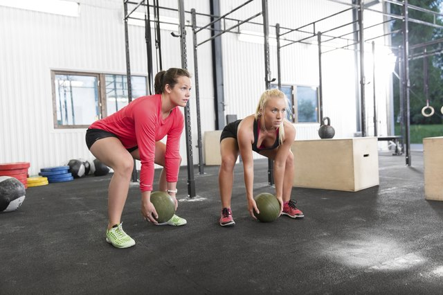 Two women lifts crossfit slam balls
