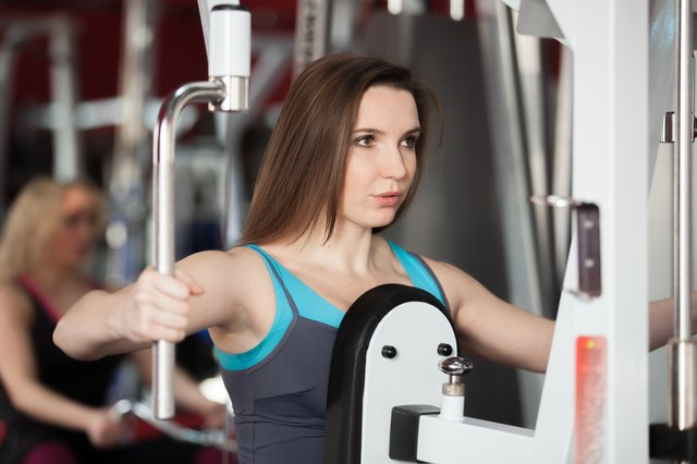 Girl exhales while doing exercises with weights on training appa
