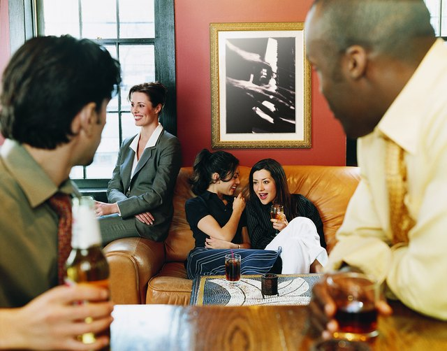 Businessmen Sitting at a Bar Watching Businesswomen Sitting on a Sofa