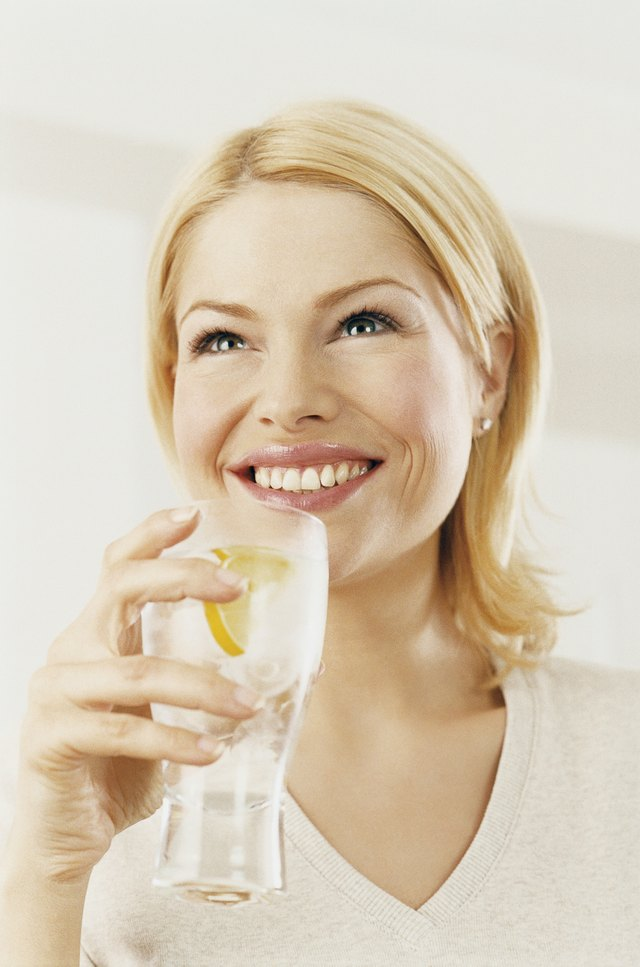 Portrait of a Woman Enjoying a Drink of Water With a Slice of Lemon